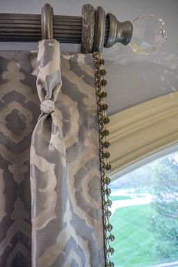 The combination of silver metallic wooden poles, crystal finials, beaded trim, button detail, tiebacks and lush fabric produced this stunning custom window treatment scheme in this formal master bedroom.